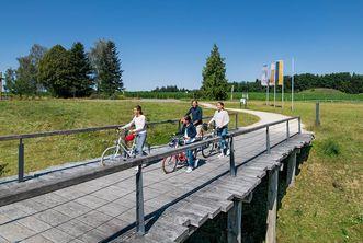 Eine Familie schiebt ihre Räder über die Eingangsbrücke